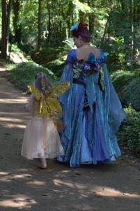 A queen and a wee faery wander in the garden.